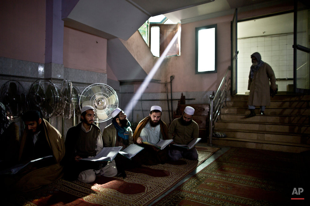 In this Sunday, Jan. 18, 2015 photo, Pakistani students of a madrassa, or Islamic school, attend their class at a seminary in Rawalpindi, Pakistan. Their white skull caps signify that they are students at one of the tens of thousands of religious schools across the country that have become embroiled in a debate about where militancy comes from.(AP Photo/Muhammed Muheisen)