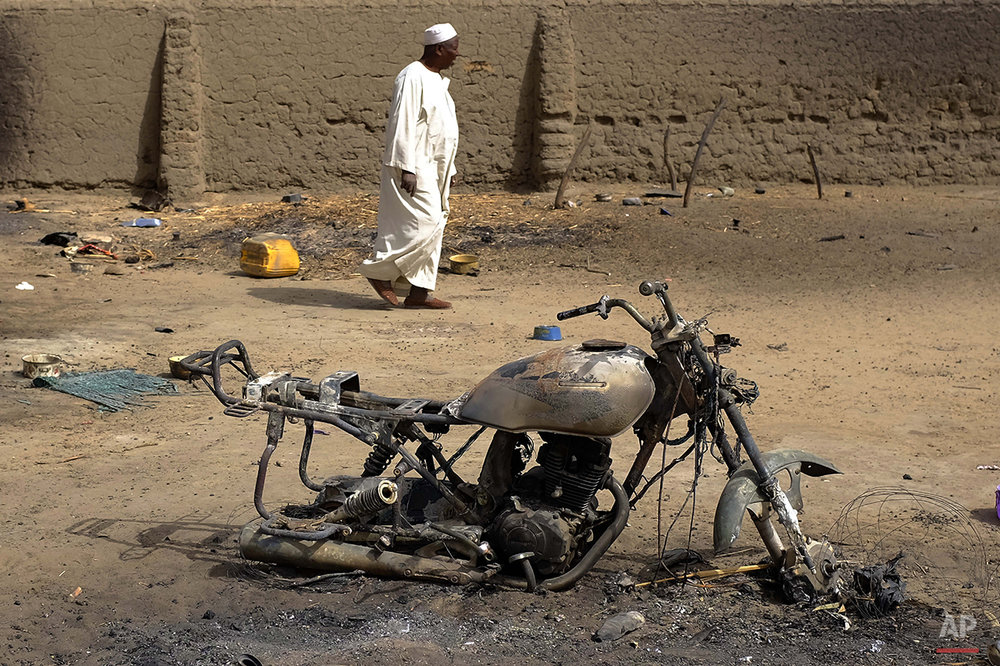 A man walks past a charred motorcycle in the Lake Chad shore village of N'Gouboua, Thursday, March 5, 2015. Boko Haram militants arrived in N'gouboua before dawn on Feb. 13, marking the first attack of its kind on Chad. By the time the scorched-earth attack ended, they had burned scores of mud-brick houses by torching them with gasoline and had killed at least eight civilians and two security officers. Some 3,400 Nigerian refugees had been living in the village at the time of the attack, and all have since been relocated further inland. (AP Photo / Jerome Delay)