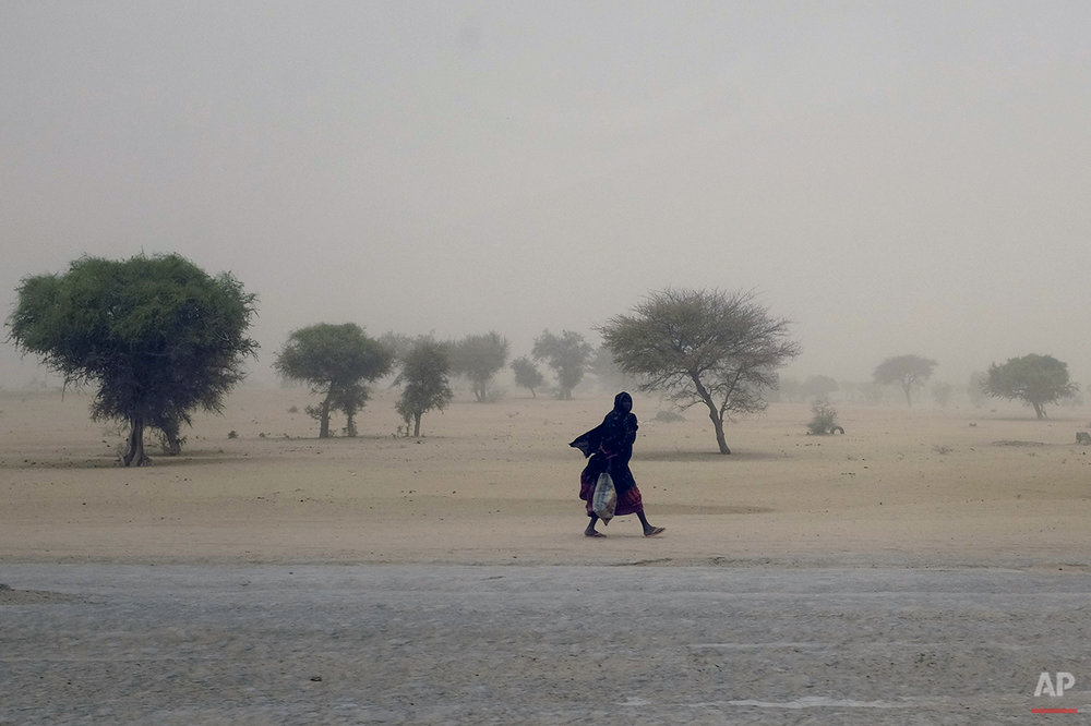 A woman walks in a sand storm near Lake Chad, in Chad, Tuesday March 3, 2015. Chadian troops have seized a strategically located northeast Nigerian town from Boko Haram, but not before the defeated Islamic extremists killed hundreds of civilians, Chad's military said. The Chadian forces regained control Monday of Dikwa, a town occupied by the militants for weeks, said Chad's military spokesman Col. Azem Bermandoua.(AP Photo / Jerome Delay)