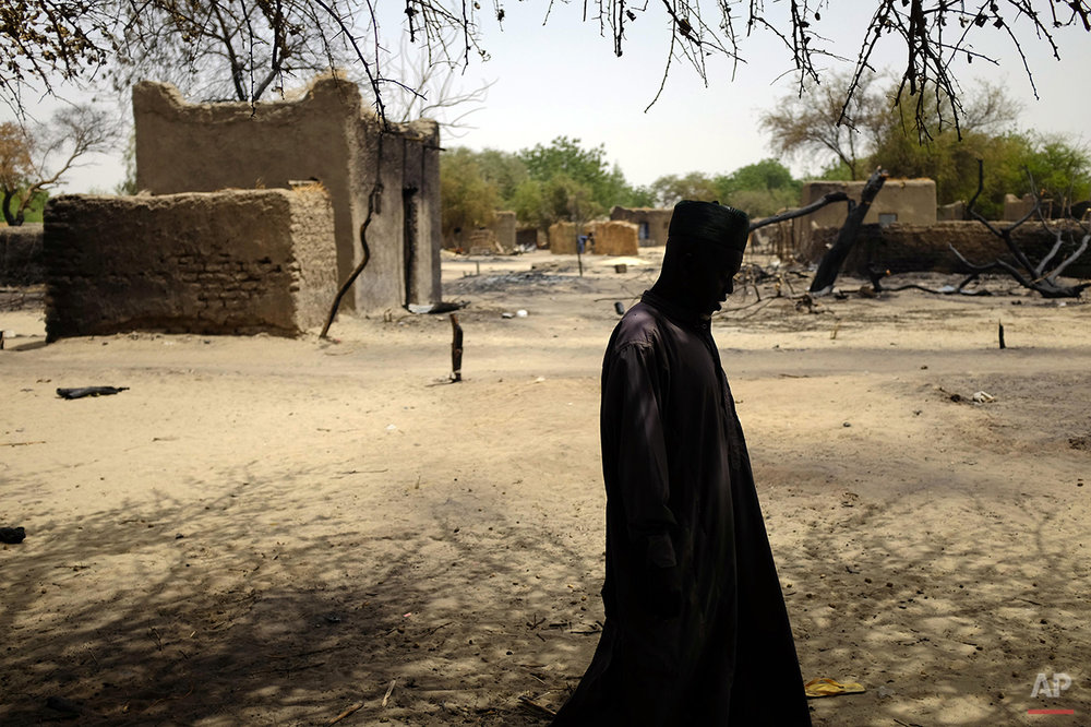 A Chadian man walks past burnt homes in the Lake Chad shore village of  N'Gouboua Thursday March 5, 2015. Boko Haram militants arrived in N'gouboua before dawn on Feb. 13, marking the first attack of its kind on Chad. By the time the scorched-earth attack ended, they had burned scores of mud-brick houses by torching them with gasoline and had killed at least eight civilians and two security officers. Some 3,400 Nigerian refugees had been living in te village at the time of the attack, and all have since been relocated further inland. (AP Photo / Jerome Delay)