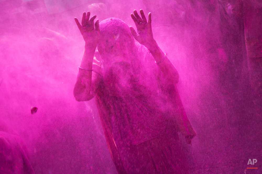 In this Tuesday, March 3, 2015 photo, a widow raises her hands as others throw colored powder on her during celebrations marking Holi at the Meera Sahabhagini WidowAshram in Vrindavan, India. The widows celebrated the Hindu festival of colors at the ashram. (AP Photo/Bernat Armangue)