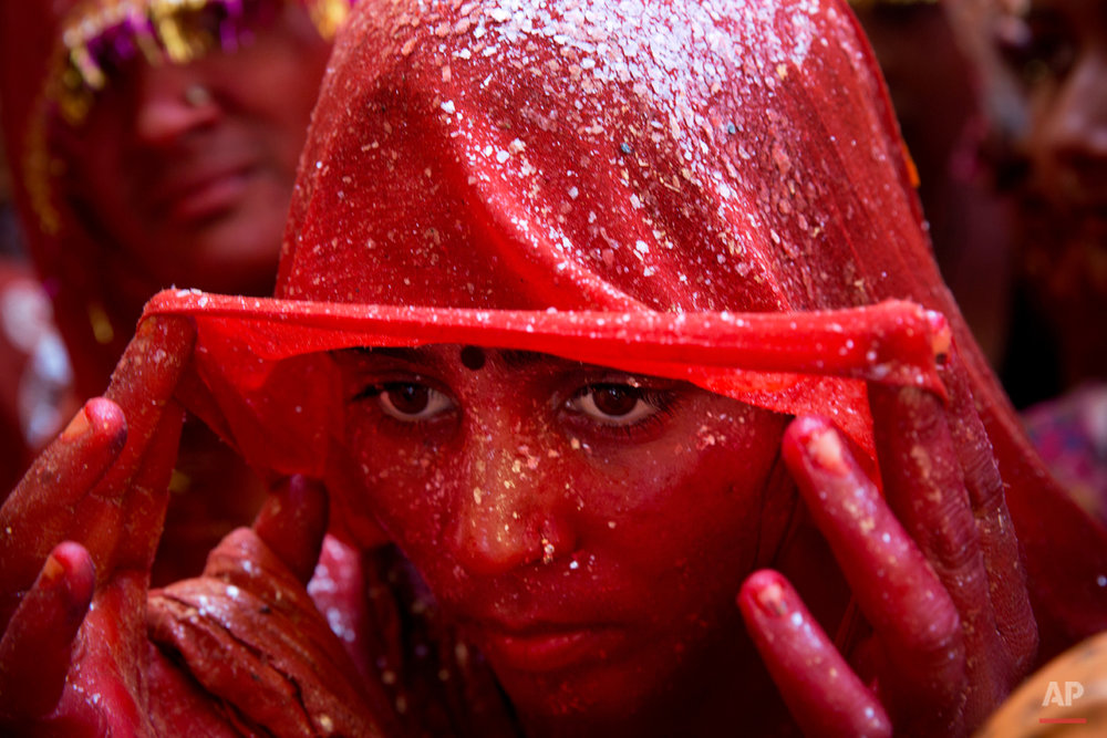 "A Hindu woman devotee lifts her veil as she stands drenched in colored water during ""Huranga,"" celebrated as part of Holi, the Hindu festival of colors, at the Baldev Temple in Dauji, 180 kilometers (113 miles) south of New Delhi, India, Saturday, March 7, 2015. During Huranga women playfully hit men with cloth whips as men drench them with buckets of colored water. (AP Photo/Bernat Armangue)"