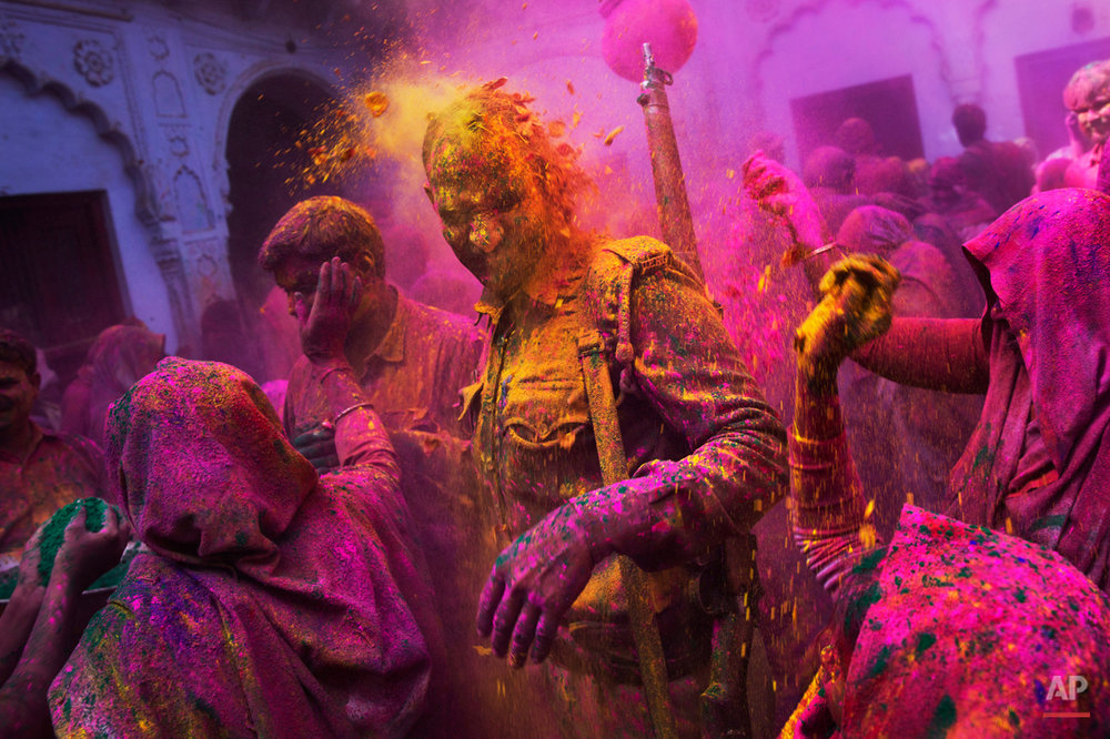 Hindu widows throw colored powder on an Indian policeman as they celebrate Holi, the Hindu festival of colors, at the Meera Sahabhagini Widow Ashram in Vrindavan, India, Tuesday, March 3, 2015. The widows, many of whom at times have lived desperate lives in the streets of the temple town, celebrated the Hindu festival of colors at the ashram. (AP Photo/Bernat Armangue)