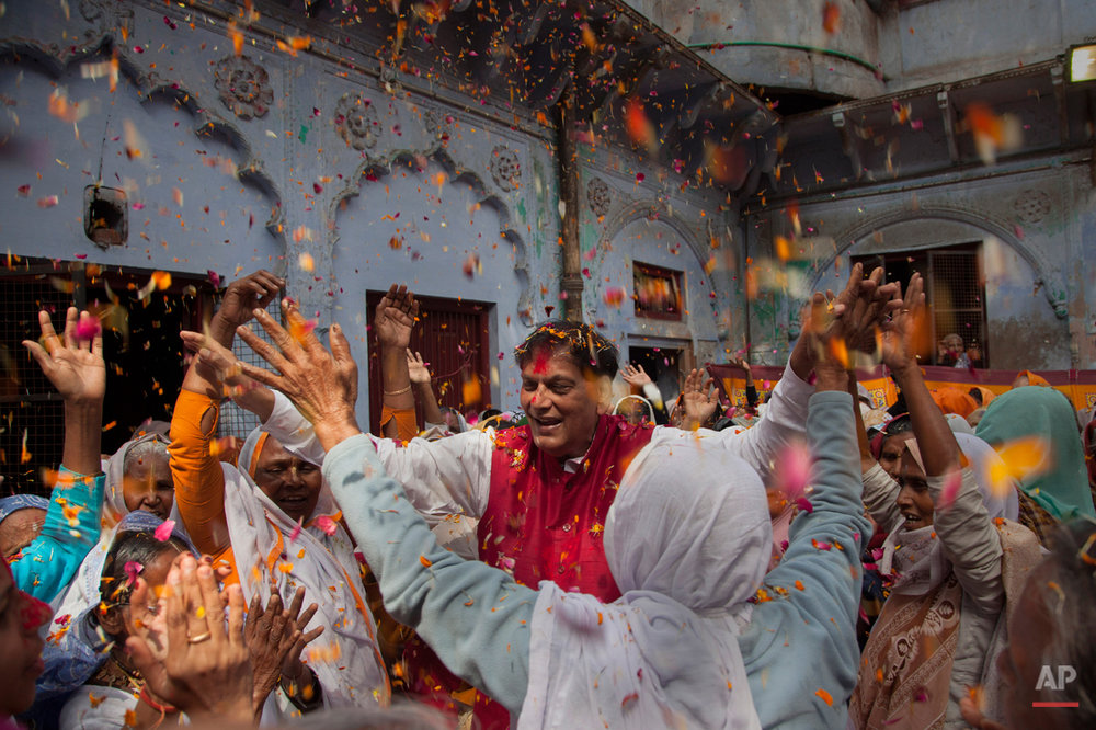 Indian Hindu widows dance with  Bindeshwar Pathak, founder of non-governmental organization Sulabh International, as they celebrate Holi at the  Meera Sahabhagini Widow Ashram in Vrindavan, India, Tuesday, March 3, 2015. The widows, many of whom at times have lived desperate lives in the streets of the temple town, celebrated the Hindu festival of colors at the ashram. (AP Photo/Tsering Topgyal)