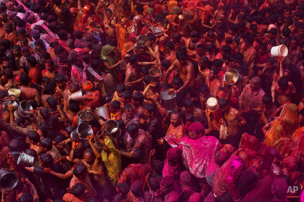 "Indian Hindu devotees walk with empty buckets after emptying the contents on women participating in ""Huranga,"" during celebrations marking Holi, the Hindu festival of colors, at the Baldev Temple in Dauji, 180 kilometers (113 miles) south of New Delhi, India, Saturday, March 7, 2015. During Huranga women playfully hit men with cloth whips as men drench them with buckets of colored water. (AP Photo/Bernat Armangue)"