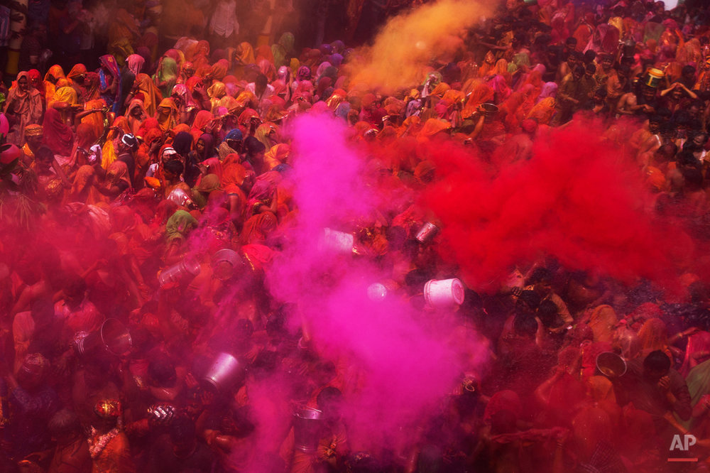 "Colored powder and water is thrown as Hindu devotees participate in ""Huranga,"" during celebrations marking Holi, the Hindu festival of colors, at the Baldev Temple in Dauji, 180 kilometers (113 miles) south of New Delhi, India, Saturday, March 7, 2015. During Huranga women playfully hit men with cloth whips as men drench them with buckets of colored water. (AP Photo/Bernat Armangue)"