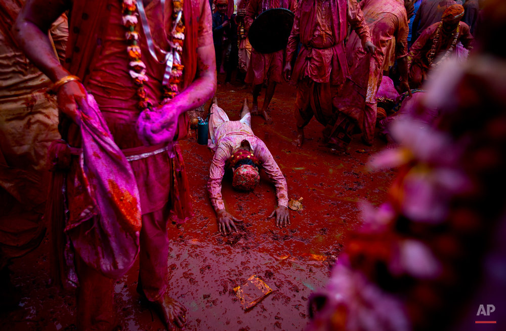 An Indian Hindu devotee from Barsana village prostrates amid colors as he prays at the Nandagram temple, famous for Lord Krishna and his brother Balram, during Lathmar holi festival, in Nandgaon, India, Saturday, Feb. 28, 2015. During Lathmar Holi the women of Nandgaon, the hometown of Krishna, beat the men from Barsana, the legendary hometown of Radha, consort of Hindu God Krishna, with wooden sticks in response to their teasing as they depart the town. (AP Photo/Saurabh Das)