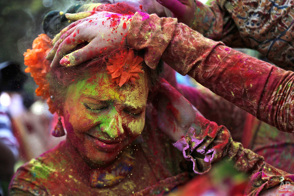 In this Thursday, March 5, 2015 photo, people smear colored powder on the face of a girl as they celebrate Holi in Kolkata, India. (AP Photo/Bikas Das)