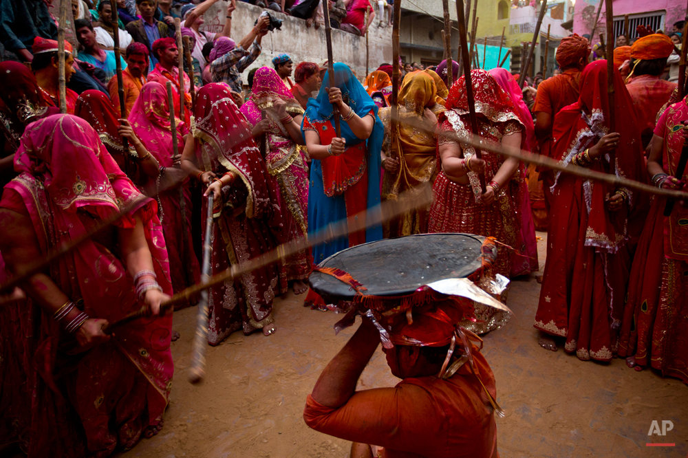 In this Saturday, Feb. 28, 2015 photo, Indian Hindu women from Nandgaon village beat the shield of a man from Barsana during Lathmar festival celebrations in Nandgaon, India. During Lathmar Holi the women of Nandgaon, the hometown of Krishna, beat the men from Barsana, the legendary hometown of Radha, consort of Hindu God Krishna, with wooden sticks in response to their teasing. (AP Photo/Saurabh Das)