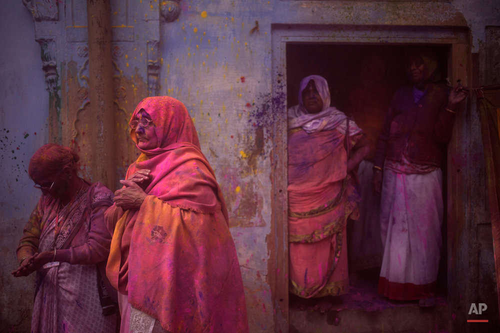 In this Tuesday, March 3, 2015 photo, Indian Hindu widows stand covered with colored powder after celebrations marking Holi at the Pagal Baba Ashram in Vrindavan, India. The widows, many of whom at times have lived desperate lives in the streets of the temple town, celebrated the Hindu festival of colors at the ashram. (AP Photo/Tsering Topgyal)