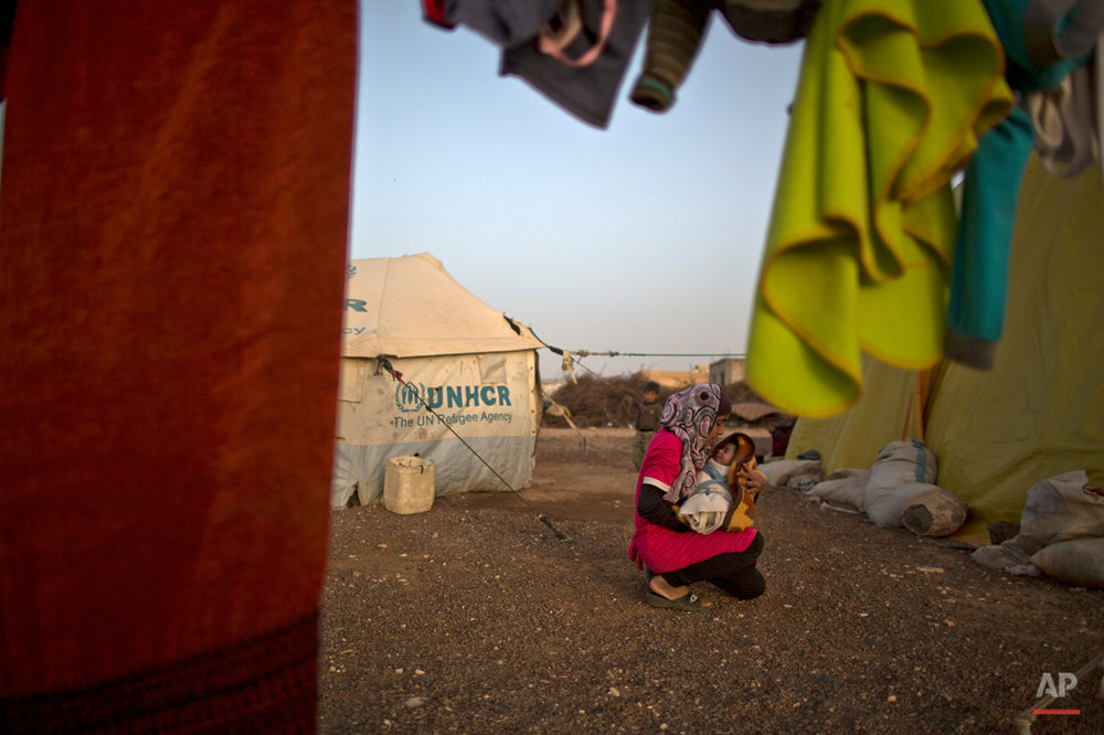 In this Saturday, March 7, 2015 photo, Syrian refugee Firyal Jumaa, 13, holds her 20 day-old sister Malak outside their tent at an informal tented settlement on the outskirts of Mafraq, Jordan. Overall, nearly 3.8 million Syrians have fled their country and are now registered as refugees, according to the agency. Most face increasingly desperate circumstances as the conflict back home enters its fifth year this week. (AP Photo/Muhammed Muheisen)