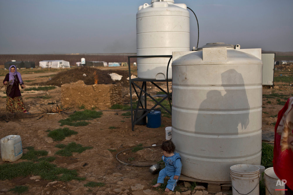 In this Sunday, March 8, 2015 photo, the shadow of a Syrian refugee woman tending to her child is cast on a water reserve at an informal tented settlement near the Syrian border, on the outskirts of Mafraq, Jordan. In Jordan, most refugees settle in urban areas. Just over 100,000 live in the three main authorized refugee camps in northern Jordan.(AP Photo/Muhammed Muheisen)