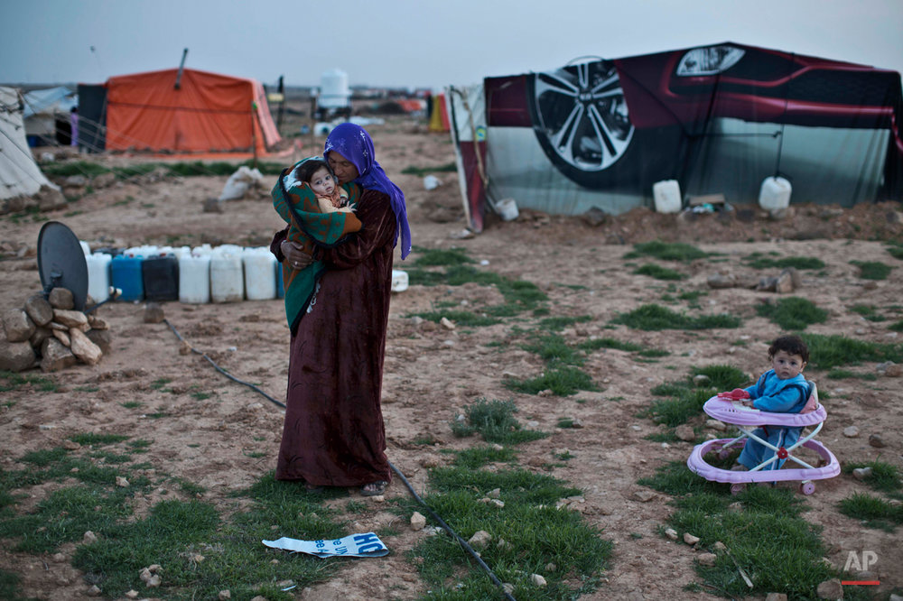 In this Sunday, March 8, 2015 photo, Syrian refugee Rifaa Ahmad, 50, cuddles her granddaughter at an informal tented settlement near the Syrian border, on the outskirts of Mafraq, Jordan. Some Syrian refugees say they pitched tents to be close to jobs on farms, especially during harvest season. Others say they can't afford rent or that they don't want to live in the authorized camps because of restrictions there. (AP Photo/Muhammed Muheisen)