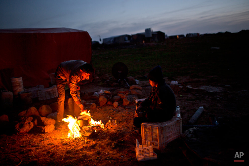 In this Sunday, March 8, 2015 photo, Syrian refugee Mohammed al-Awad, 19, left, cooks for his brother Abdulelah, 14, using a fire outside their tent at an informal tented settlement near the Syrian border, on the outskirts of Mafraq, Jordan. Aid officials say those in the makeshift camps are among the most vulnerable of close to 625,000 Syrians who fled to Jordan and have registered with the U.N. refugee agency. (AP Photo/Muhammed Muheisen)