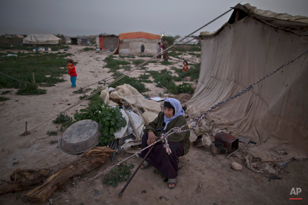 In this Friday, March 6, 2015 photo, an elderly Syrian refugee sits outside of her tent at an informal tented settlement in the Jordan Valley, Jordan. Dozens of small, makeshift tent settlements have sprung up across Jordan, home to thousands of Syrian refugees who don't want to live in large, government-supervised refugee camps but can't afford to live in Jordanian towns and cities. (AP Photo/Muhammed Muheisen)