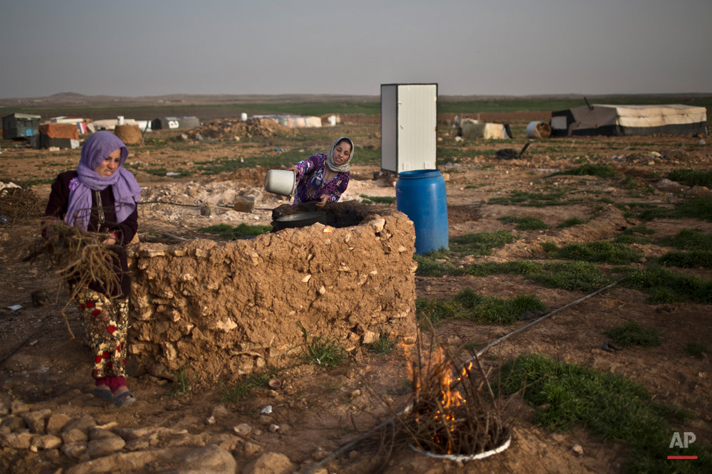 In this Sunday, March 8, 2015 photo, a Syrian refugee boils water as another woman carries fire wood at an informal tented settlement near the Syrian border, on the outskirts of Mafraq, Jordan. Overall, nearly 3.8 million Syrians have fled their country and are now registered as refugees, according to the agency. Most face increasingly desperate circumstances as the conflict back home enters its fifth year this week. (AP Photo/Muhammed Muheisen)