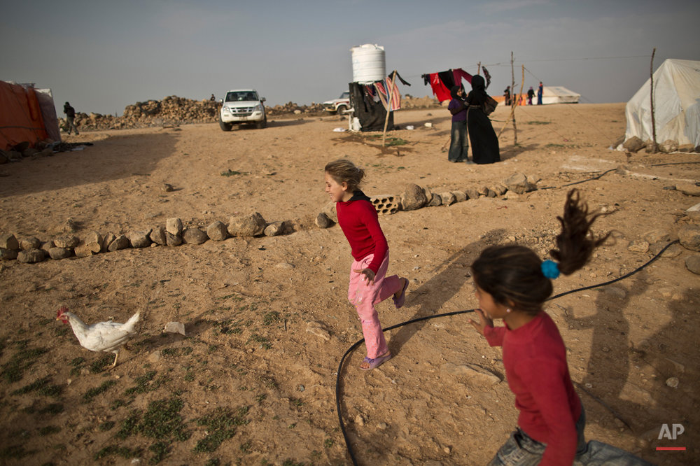 In this Sunday, March 8, 2015 photo, Syrian refugee girls chase a chicken while playing at an informal tented settlement on the outskirts of Mafraq, Jordan. Aid officials say those in the makeshift camps are among the most vulnerable of close to 625,000 Syrians who fled to Jordan and have registered with the U.N. refugee agency.(AP Photo/Muhammed Muheisen)