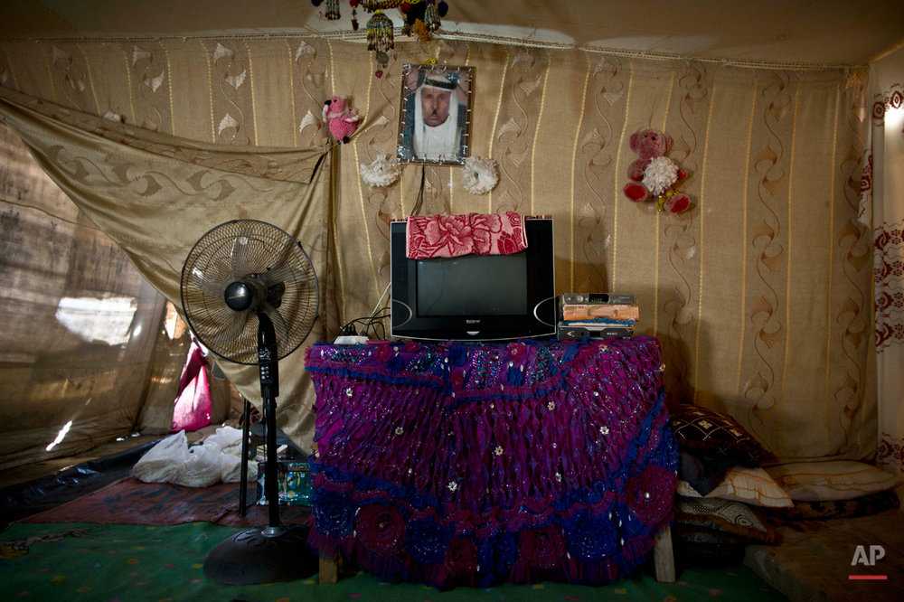 In this Friday, March 6, 2015 photo, a framed photograph of Syrian refugee Shahada Hussein, who passed away in 2014, hangs inside his son's tent at an informal tented settlement in the Jordan Valley, Jordan. Aid officials say those in the makeshift camps are among the most vulnerable of close to 625,000 Syrians who fled to Jordan and have registered with the U.N. refugee agency. (AP Photo/Muhammed Muheisen)