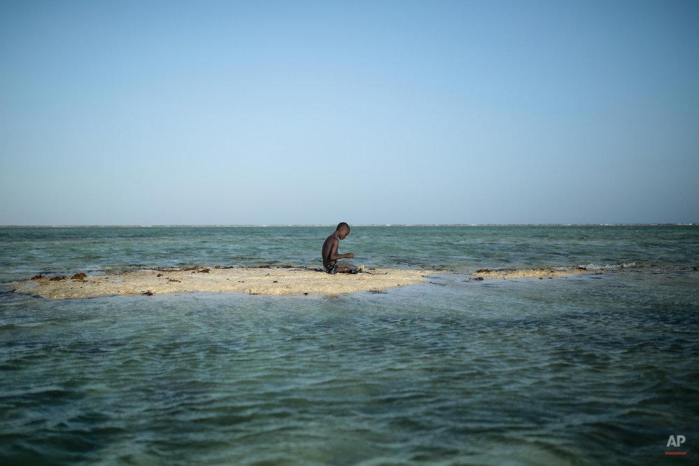 A young Zanzibari fisherman takes a break on a sandbank in the Indian Ocean off the coast of Matemwe village, northeastern Zanzibar, Tanzania, Wednesday, Jan. 28, 2015. (AP Photo/Mosa'ab Elshamy)