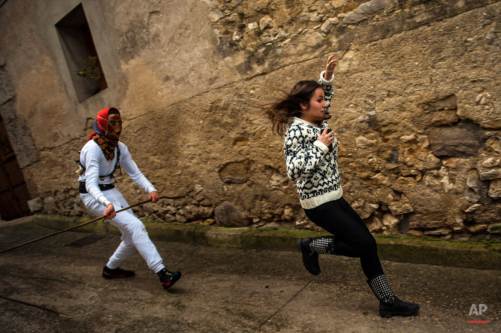 In this photo taken on Sunday, Feb. 15, 2015 a girl runs away from a ''Mamuxarro'' during the carnival, in the small town of Unanu, northern Spain. While Rio de Janeiro may boast the worldís most famous carnival, the festive period of masquerades and wild and colorful costumes that precedes the Christian religious season of Lent is also a permanent and popular fixture for celebration in Spain and Portugal, with each country having its own strange and unique way of doing it. In the northern Spanish ancient village of Unamu, people dress up as 'Mamuxarroí, folkloric figures in white with a red sash and a metal mask to cover their faces as they pursue townsfolk with sticks. According to custom, their 'victims' (usually young women) must kneel and kiss the mamuxarroís knee after he makes the sign of the cross on their forehead. (AP Photo/Alvaro Barrientos)