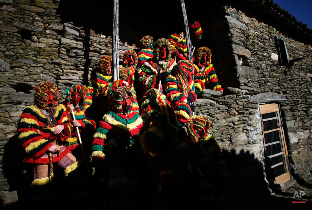 In this photo taken on Tuesday, Feb. 17, 2015 revelers from the Portuguese village of Podence dressed in traditional costumes pose for photographers during annual Carnival festivities, in Podence, northeastern Portugal.  While Rio de Janeiro may boast the worldís most famous carnival, the festive period of masquerades and wild and colorful costumes that precedes the Christian religious season of Lent is also a permanent and popular fixture for celebration in Spain and Portugal, with each country having its own strange and unique way of doing it. Portugalís most famous carnival takes place in the north-central town of Lazarin, with its pagan ëcaretoí ritual of masked young men dressed in colored woolen quilts and donning brass, leather or wooden masks as they dance and chase local people _ especially young women _ through the streets, trying to scare them by making lots of noise and jingling bells on their backs. (AP Photo/Francisco Seco)
