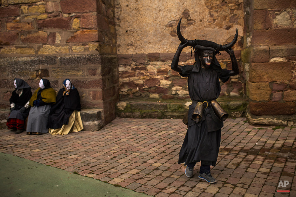 In this photo taken on  Saturday, Feb. 14, 2015 a man, covered in oil and soot carrying bull horns on his head and cowbells on a belt representing the devil, walks  away from people wearing costumes during a traditional carnival celebration in the small village of Luzon, Spain. While Rio de Janeiro may boast the worldís most famous carnival, the festive period of masquerades and wild and colorful costumes that precedes the Christian religious season of Lent is also a permanent and popular fixture for celebration in Spain and Portugal, with each country having its own strange and unique way of doing it. In Spainís central town of Luzon, men covered in oil and soot wear bull horns and cowbells to represent the devil. Records of Luzonís carnival date as far back as the 14th century although it is believed to be much older. (AP Photo/Andres Kudacki)