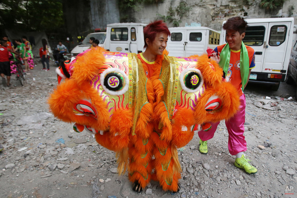 In this Wednesday, Feb. 18, 2015, photo, a Pink Panther Dragon and Lion Dance Group dancer, Jhayvee Sicat, laughs with another dancer as he carries Chinese lion heads to their next performance in the Chinatown area of Manila, Philippines. Recently, about twenty five dancers from the dance group went to an office with their drums and costumes to perform and take selfies with workers.(AP Photo/Aaron Favila)