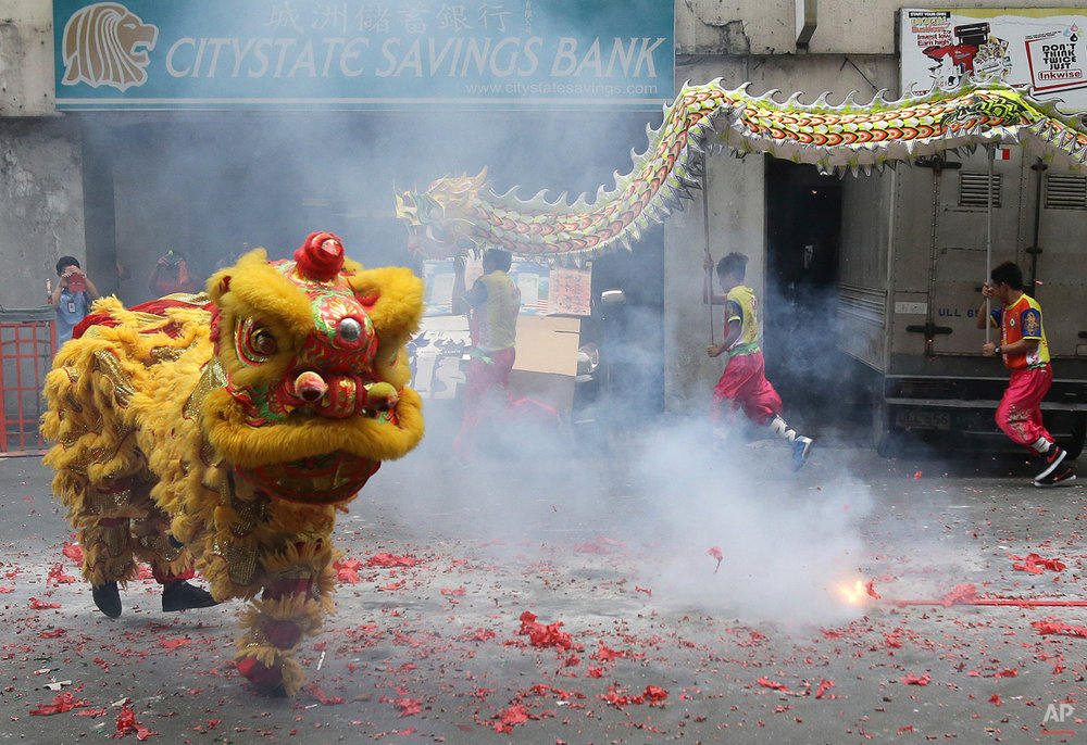 In this Wednesday, Feb. 18, 2015, photo, Filipino lion and dragon dancers perform in the Chinatown area of Manila, Philippines. The dance group's busiest season is during the Lunar New Year. (AP Photo/Aaron Favila)