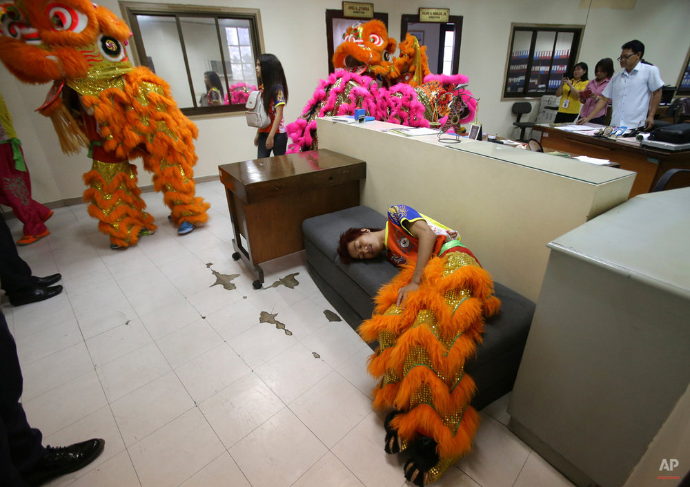 In this Wednesday, Feb. 18, 2015, photo, Filipino lion dancer Jhayvee Sicat takes a break after a performance at the Manila Central Post Office in Manila, Philippines. The dancers are busiest during the Lunar New Year. (AP Photo/Aaron Favila)