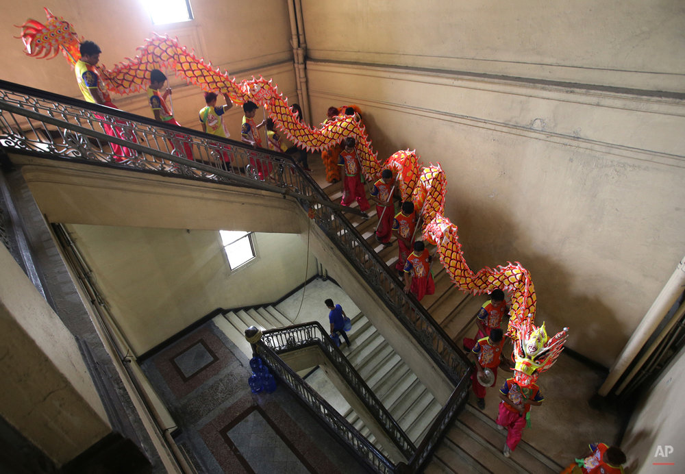 In this photo taken on Wednesday, Feb. 18, 2015, Filipino lion and dragon dancers walk down a staircase at the Manila Central Postal Office as they head to their next performance in Manila, Philippines on Wednesday, Feb. 18, 2015. The dance company currently has nine dragons and a team of 100 workers. (AP Photo/Aaron Favila)