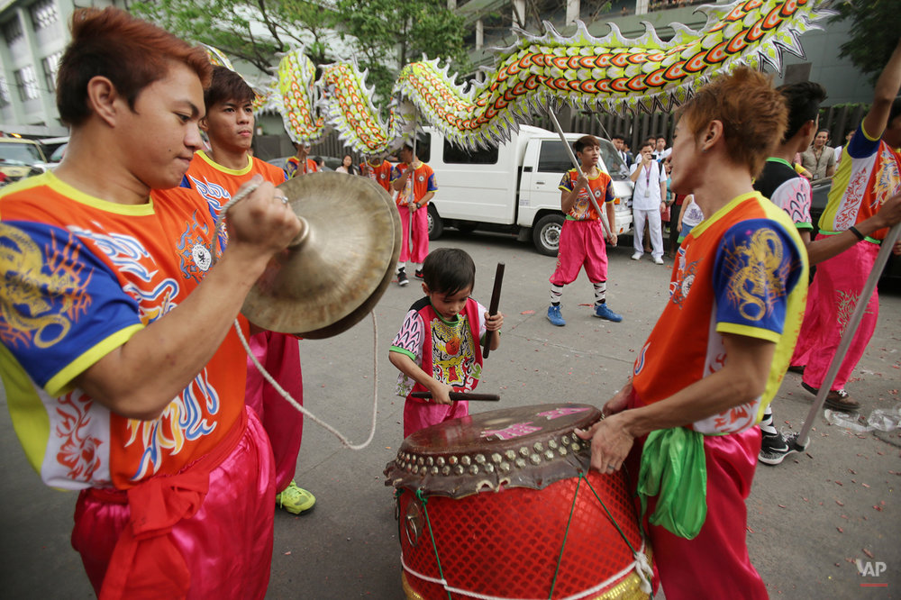 In this Wednesday, Feb. 18, 2015, photo, Thristan Rain Sicat, 7,  performs as his father Therry, right, holds the drums during their lion and dragon dance performance in Manila, Philippines. The dance group is hired by businesses that believe the show will drive misfortunes away and bring good luck. (AP Photo/Aaron Favila)