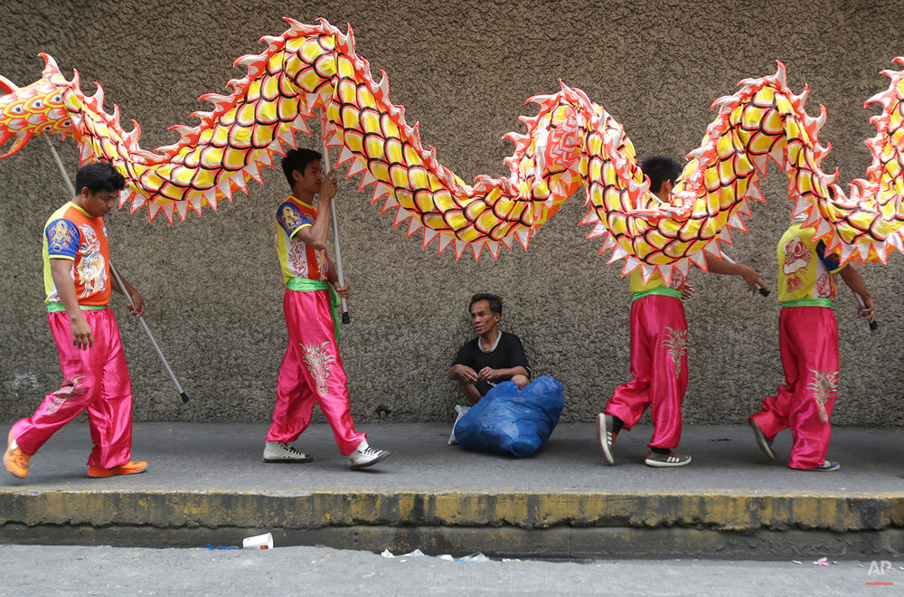 In this Wednesday, Feb. 18, 2015, photo, Filipino dragon dancers walk to their next performance in Manila, Philippines.  During the Chinese New Year week dancers can usually get as much as 1,000 pesos ($23) per day. (AP Photo/Aaron Favila)