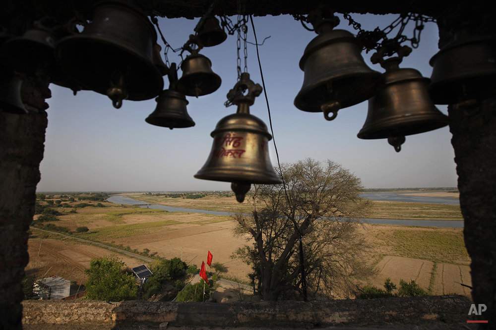 In this photo taken Tuesday, April 29, 2014, bells hang from an old temple built near the confluence of the rivers Yamuna, front, and Chambal, background, in Bhareh village in the northern Indian state of Uttar Pradesh. The fears that shaped this region go back more than a thousand years, to when sages said the Chambal, the term refers both to the river and the rugged land around it, had been cursed and villagers whispered that it was unholy. In a culture where rivers have long been worshipped, farmers avoided planting along the river's banks. (AP Photo/Altaf Qadri)