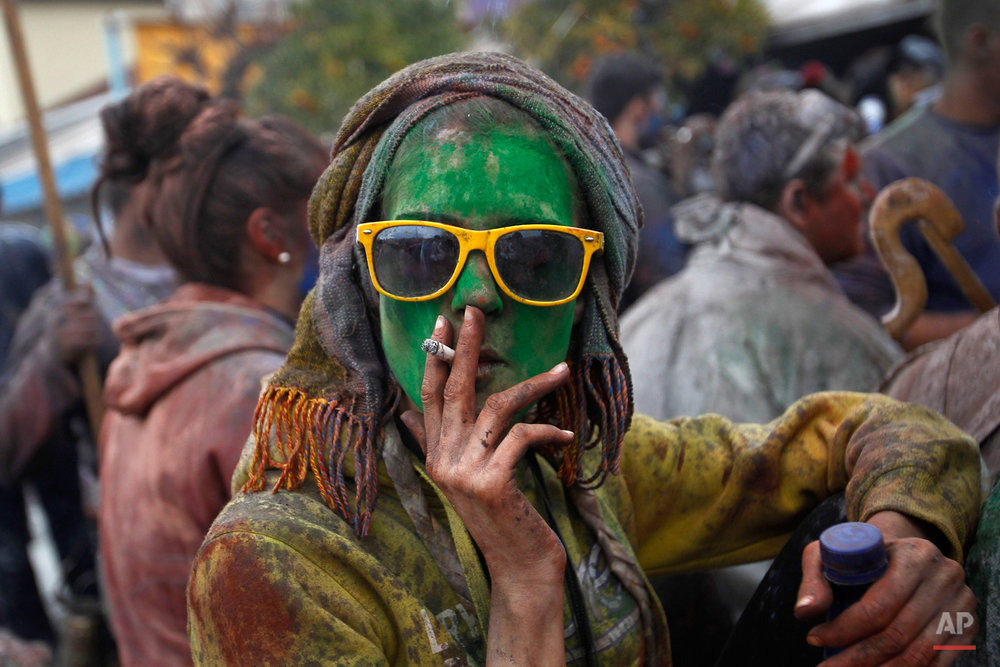 A local reveler smokes a cigarette as she celebrate Clean Monday with a flour war, a unique colorful flour fight marking the end of the carnival season in the port town of Galaxidi, some 200 kilometers (120 miles) west of Athens, Monday, Feb. 23, 2015. The flour fight, on the coastal road lining Galaxidiís old harbor, takes place on Clean Monday, the beginning of the 40-day Christian Lent fast that ends on Easter Sunday. Although Clean Monday ceremonies abound across Greece, the most common being kite-flying, Galaxidiís flour-fight is unique, and is thought to have been influenced by similar goings-on in Sicily in the 19th century. (AP Photo/Petros Giannakouris)