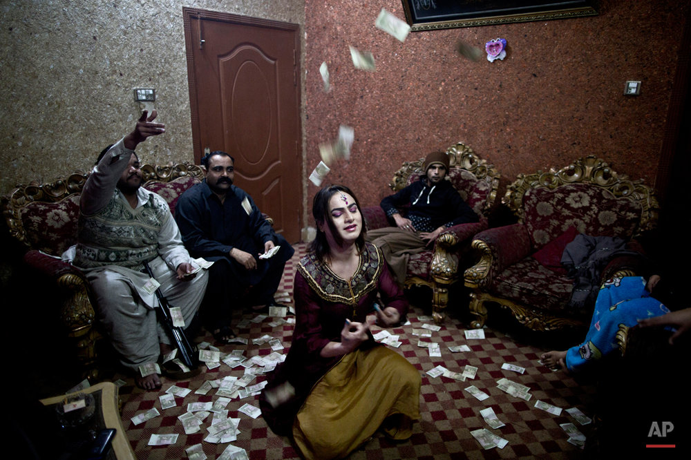 In this Thursday, Jan. 15, 2015 photo, Pakistani Waseem Akram, 27, dances during a private party in Rawalpindi, Pakistan. By day, Akram sells mobile phone accessories from an alleyway shop in an old neighborhood of this Pakistani city. But by night, he stands before a mirror, shaving away his beard and picking through mascara and rouge to become Rani, a female wedding party dancer. ìBeing a dancer at weddings, parties and private events ... helps me earn much more money than working in a shop,î Akram said. (AP Photo/Muhammed Muheisen)