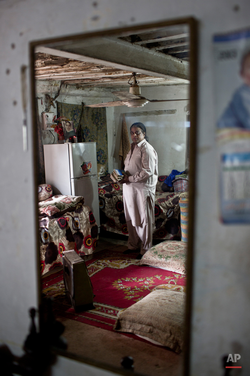 In this Thursday, Jan. 8, 2015 photo, Pakistani Amjad Mahmoud, 44, is reflected in a mirror while posing for a picture at his place, in Rawalpindi, Pakistan. Across conservative Pakistan, where Islamic extremists launch near-daily attacks and many follow a strict interpretation of their Muslim faith, those like Amjad face a challenge of balancing two identities. Some left their villages for the anonymity of a big city, fearing the reactions of their families while still concealing identity from neighbors and co-workers. (AP Photo/Muhammed Muheisen)
