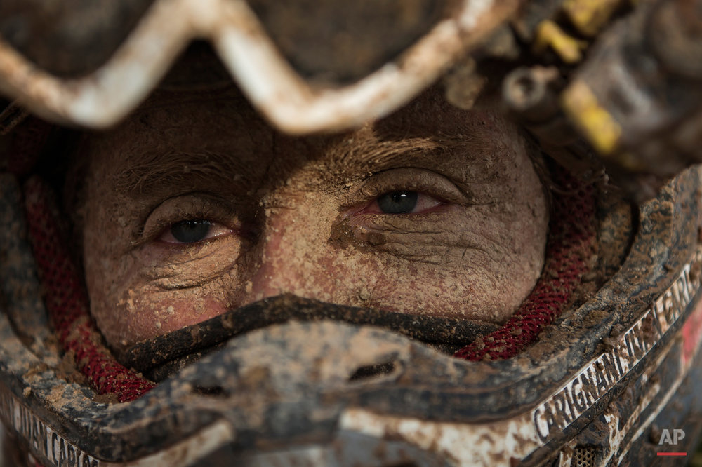 Yamaha quad rider Juan Carlos Carignani, from Italy, arrives with his face covered in dirt at the Uyuni camp after completing the seventh stage of the Dakar Rally 2015 between Iquique, Chile, and Uyuni, Bolivia, Sunday, Jan. 11, 2015. The race will finish on Jan. 17, passing through Bolivia and Chile before returning to Argentina where it started. (AP Photo/Felipe Dana)
