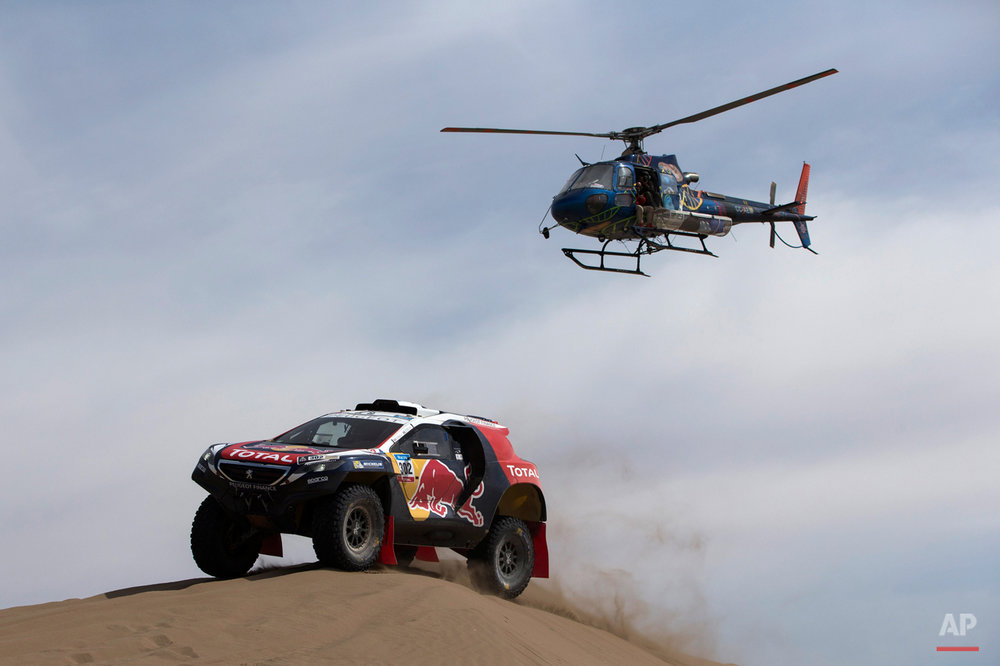 A Dakar helicopter flies over Peugeot driver Stephane Peterhansel and co-pilot Jean Paul Cottret, both of France, as they race through the dunes during the ninth stage of the Dakar Rally 2015 between the cities of Iquique and Calama, Chile, Tuesday, Jan. 13, 2015. The race will finish on Jan. 17, passing through Bolivia and Chile before returning to Argentina where it started. (AP Photo/Felipe Dana)