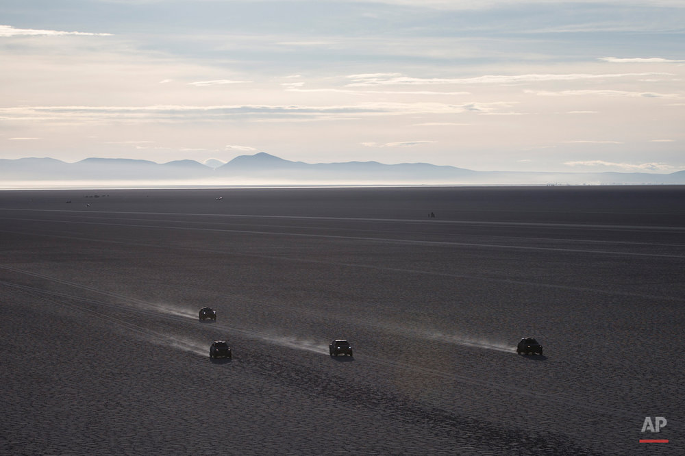 Competitors race across the Uyuni salt flats during the eighth stage of the Dakar Rally 2015 between Uyuni, Bolivia, and Iquique, Chile, Sunday, Jan. 11, 2015. The race will finish on Jan. 17 in Argentina where it started. (AP Photo/Felipe Dana)