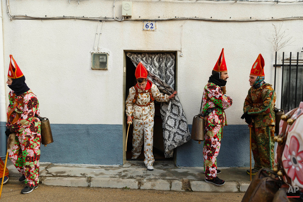 "Members of the Endiablada brotherhood pause before walking around the village during the 'Endiablada' traditional festival in Almonacid Del Marquesado, Spain, Tuesday, Feb. 3, 2015. The ""Endiablada"" (The Brotherhood of the Devils) festivals are celebrated each Feb. 2-3 in the central Spanish town of Almonacid del Marquesado since medieval times or before. In the festival, men from the town dress up as devil-type characters in colorful jumpsuit costumes and red miter hats. They don large heavy copper cowbells around their waists, which clang incessantly as they walk, dance and jump through the town's winding streets and visit the cemetery. The Feb. 3 day procession commemorates the day of Saint Blas. According to a local legend, town shepherds found a statue of the saint and then won a competition with folk from a nearby town to keep the effigy and rang the bells of their animals in celebration. (AP Photo/Daniel Ochoa de Olza)"