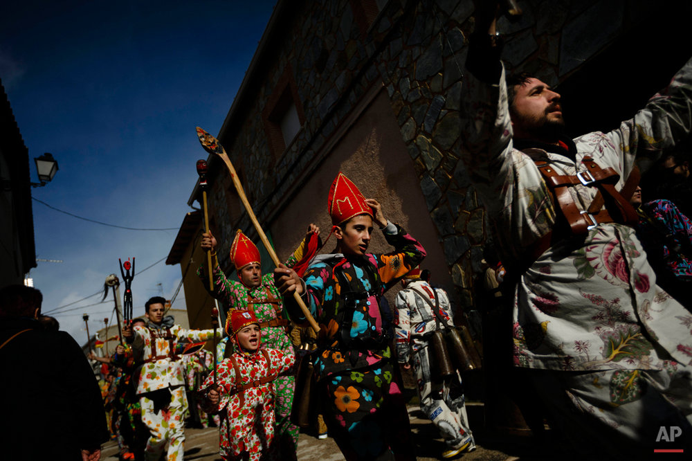 "Members of the Endiablada brotherhood dance during the 'Endiablada' traditional festival in Almonacid Del Marquesado, Spain, Tuesday, Feb. 3, 2015. The ""Endiablada"" (The Brotherhood of the Devils) festivals are celebrated each Feb. 2-3 in the central Spanish town of Almonacid del Marquesado since medieval times or before. In the festival, men from the town dress up as devil-type characters in colorful jumpsuit costumes and red miter hats. They don large heavy copper cowbells around their waists, which clang incessantly as they walk, dance and jump through the town's winding streets and visit the cemetery. The Feb. 3 day procession commemorates the day of Saint Blas. According to a local legend, town shepherds found a statue of the saint and then won a competition with folk from a nearby town to keep the effigy and rang the bells of their animals in celebration. (AP Photo/Daniel Ochoa de Olza)"