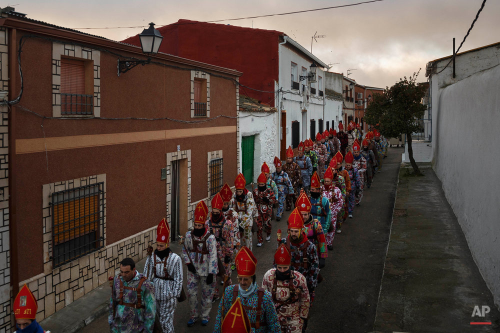 "Members of the Endiablada brotherhood march during the 'Endiablada' traditional festival in Almonacid Del Marquesado, Spain, Tuesday, Feb. 3, 2015. The ""Endiablada"" (The Brotherhood of the Devils) festivals are celebrated each Feb. 2-3 in the central Spanish town of Almonacid del Marquesado since medieval times or before. In the festival, men from the town dress up as devil-type characters in colorful jumpsuit costumes and red miter hats. They don large heavy copper cowbells around their waists, which clang incessantly as they walk, dance and jump through the town's winding streets and visit the cemetery. The Feb. 3 day procession commemorates the day of Saint Blas. According to a local legend, town shepherds found a statue of the saint and then won a competition with folk from a nearby town to keep the effigy and rang the bells of their animals in celebration. (AP Photo/Daniel Ochoa de Olza)"
