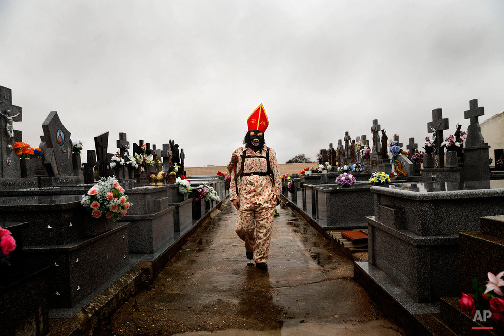 "In this Feb. 2, 2015 picture, a member of the Endiablada brotherhood walks trough the cemetery after paying respect to their deceased fellow believers and relatives during the 'Endiablada' traditional festival in Almonacid Del Marquesado, Spain. The ""Endiablada"" (The Brotherhood of the Devils) festivals are celebrated each Feb. 2-3 in the central Spanish town of Almonacid del Marquesado since medieval times or before. In the festival, men from the town dress up as devil-type characters in colorful jumpsuit costumes and red miter hats. They don large heavy copper cowbells around their waists, which clang incessantly as they walk, dance and jump through the town's winding streets and visit the cemetery. The Feb. 2 procession, the ""Candelaria"" (Candlemas), represents the Virgin Mary presenting baby Jesus to authorities in the temple 40 days after Christmas. The protocol is believed to have caused her some embarrassment and the accompanying bell-clanging characters are thought to be a way of diverting the publicís attention. (AP Photo/Daniel Ochoa de Olza)"