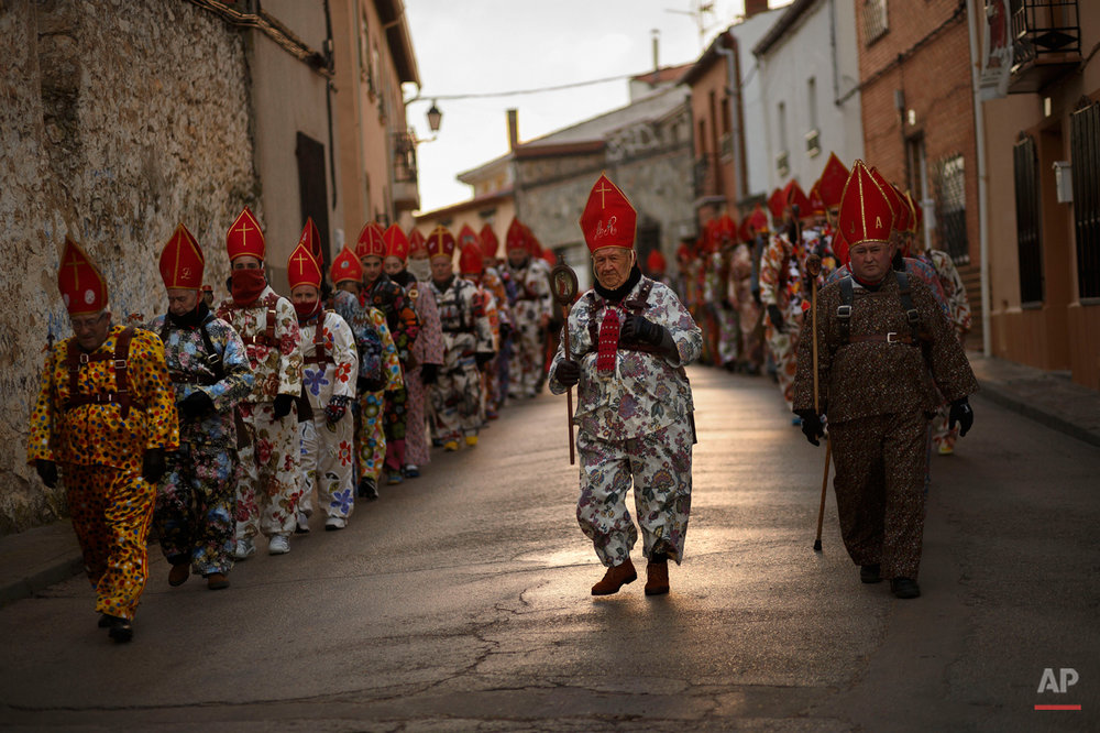 "Aniceto Rodrigo, 78, Diablo Mayor or 'greater devil', center, leads the 'Endiablada' traditional festival  in Almonacid Del Marquesado, Spain, Tuesday, Feb. 3, 2015. The ""Endiablada"" (The Brotherhood of the Devils) festivals are celebrated each Feb. 2-3 in the central Spanish town of Almonacid del Marquesado since medieval times or before. In the festival, men from the town dress up as devil-type characters in colorful jumpsuit costumes and red miter hats. They don large heavy copper cowbells around their waists, which clang incessantly as they walk, dance and jump through the town's winding streets and visit the cemetery. The Feb. 3 day procession commemorates the day of Saint Blas. According to a local legend, town shepherds found a statue of the saint and then won a competition with folk from a nearby town to keep the effigy and rang the bells of their animals in celebration. (AP Photo/Daniel Ochoa de Olza)"