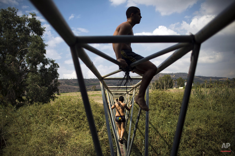 Israeli youth walk on a water pipe on the Jordan river during the week long Jewish holiday of Sukkot, near the northern Israeli town of Tiberias, Tuesday, Oct. 14, 2014. (AP Photo/Oded Balilty)