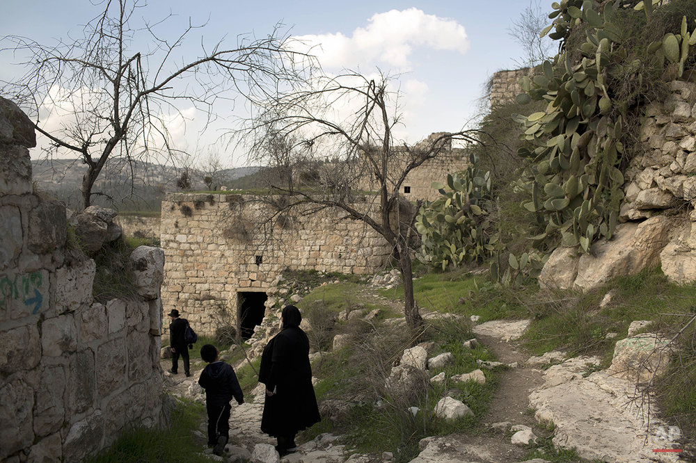 Ultra Orthodox Jewish family members tour in Lifta, located in Jerusalem's mountains, Thursday, Jan. 30, 2014. (AP Photo/Oded Balilty)