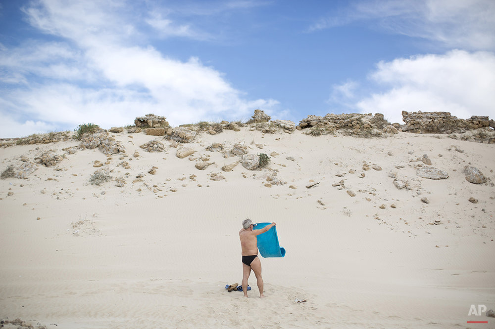 A man shakes out his towel at the beach on the Mediterranean Sea in Caesarea, northern Israel, Wednesday, Oct. 22, 2014. (AP Photo/Oded Balilty)