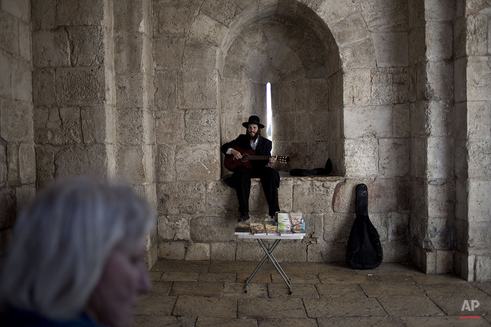 A Jewish Orthodox man plays the guitar as he sells religious books in Jerusalem's old city Jaffa Gate, Wednesday, April 30, 2014. (AP Photo/Ariel Schalit)