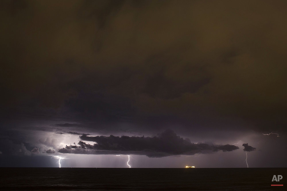 Lightning strikes down during a storm over the Mediterranean sea near a cargo ship off the coast near Michmoret, Israel, Monday, Nov. 24, 2014. (AP Photo/Ariel Schalit)