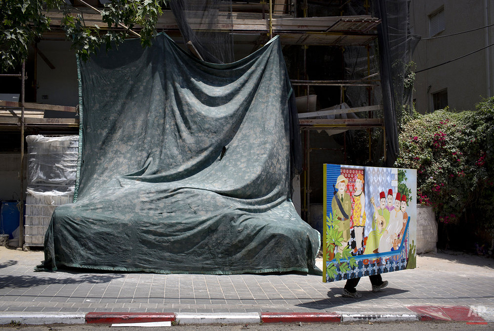A gallery worker carries a painting in downtown Tel Aviv, Israel, Monday, July 7, 2014. (AP Photo/Oded Balilty)